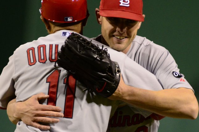 St. Louis Cardinals third base coach Jose Oquendo (11) embraces former center fielder Peter Bourjos (8) following their 11-1 win against the Pittsburgh Pirates that clinched the National League Central Division championship in game two of a doubleheader at PNC Park in Pittsburgh on September 30, 2015. Photo by Archie Carpenter/UPI