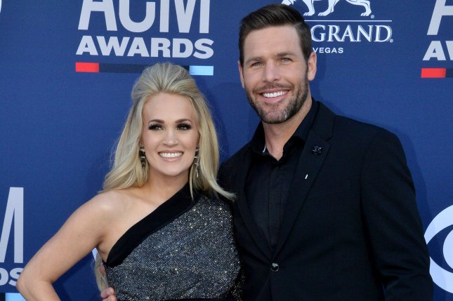 Carrie Underwood (L), pictured with Mike Fisher, recalled the emotional impact of her miscarriages. File Photo by Jim Ruymen/UPI
