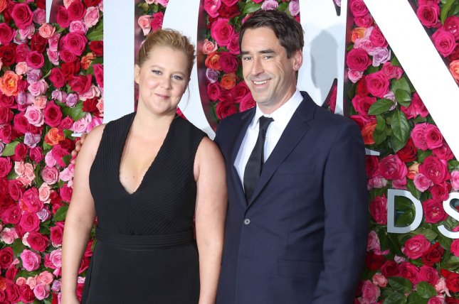Amy Schumer (L), pictured with Chris Fischer, asked fans for support and advice a week into her in vitro fertilization treatments. File Photo by Serena Xu-Ning/UPI