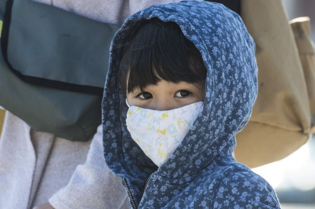 A child is seen wearing a face mask in Burlingame, Calif., on Tuesday. Beginning next Monday, all shoppers at Walmart will be required to wear a face covering, the company said. Photo by Terry Schmitt/UPI