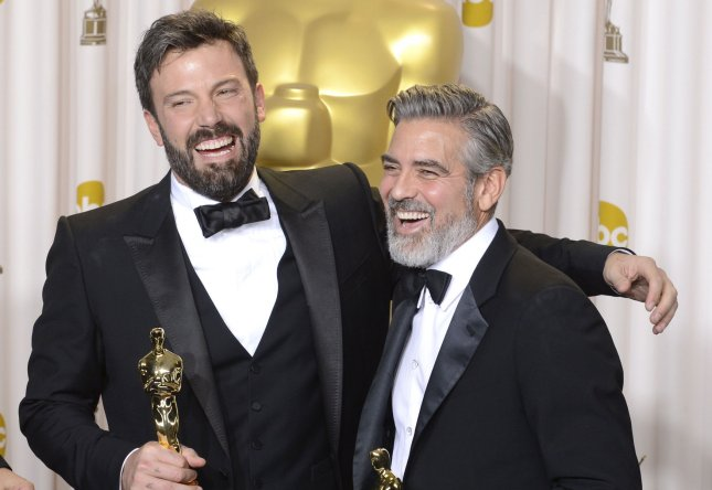 George Clooney and Ben Affleck embrace as they pose with their Oscars for Best Picture for Argo backstage at the 85th Academy Awards at the Hollywood and Highland Center in the Hollywood section of Los Angeles on February 24, 2013. UPI/Phil McCarten