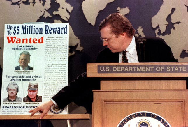 David Scheffer, U.S. ambassador-at-large for war crimes, unveils a poster at the State Department, March 2, 2000, to be distributed in Europe in an effort to step up the drive for the conviction of Yugoslav President Slobodan Milosevic and two other suspected war criminals, Radovan Karadzic and Ratko Mladic. rg/rg/Rachel Griffith UPI