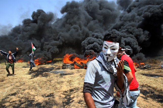 A Palestinian youth wears a mask at a protest in Khan Younis at the Israel-Gaza border Friday. Israeli troops killed several Palestinians and injured dozens more, medical sources said. Photo by Ismael Mohamad/UPI