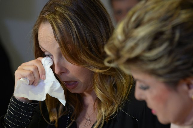 Actress and screenwriter Louisette Geiss wipes tears from her eyes as she listens to attorney Gloria Allred during a legal case involving sexual misconduct accusations against former film producer Harvey Weinstein, during a news conference in Los Angeles, Calif., on October 10, 2017. File Photo by Jim Ruymen/UPI