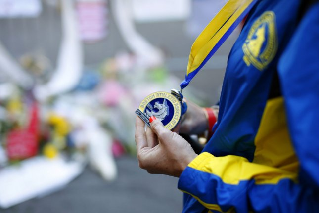 A Boston Marathon runner shows off her medal in front of a makeshift memorial for the Boston Marathon bombing victims near the site on Boylston Street in Boston, Massachusetts April 17, 2013. UPI/Matthew Healey