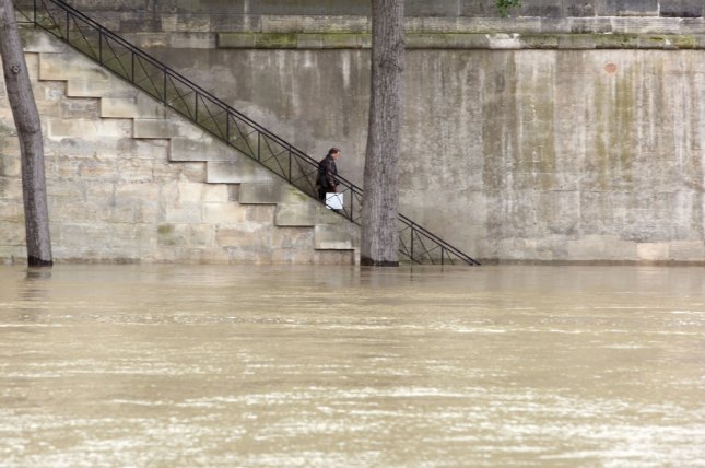 Onlookers check the waters of the Seine river after it overflowed its banks following torrential rains in Paris on June 4, 2016. The water level of the Seine is slowly decreasing after reaching a peak overnight, hitting its highest level in nearly 35 years, and authorities warned it could take up to ten days to return to normal. Photo by Maya Vidon-White/UPI