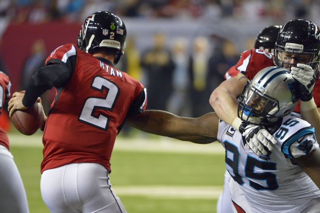 Former Carolina Panthers defensive end Charles Johnson (95) reaches out to sack quarterback Matt Ryan (2). File photo by David Tulis/UPI