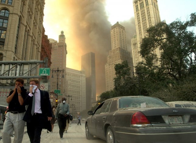 People cover their faces as they move quickly away from the World Trade Center in New York City after terrorists hijacked two commercial airplanes and crashed them into the Twin Towers on September 11, 2001. Photo by Steven E. Frischling/UPI