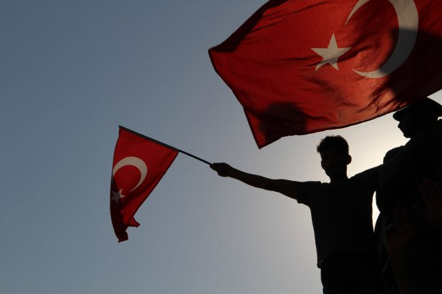 A Turkish man holds a national flag during a demonstration in Istanbul, Turkey, on July 16, 2016, following a failed coup by Turkey's military. The attempt and subsequent arrest of a U.S. pastor has led to economic turmoil in Ankara. File Photo by Hanna Noori/UPI