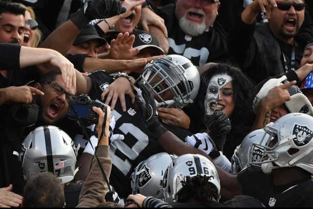 Oakland Raiders defensive end Khalil Mack (52) is mobbed in the stands after intercepting a pass by Carolina Panthers QB Cam Newton and scoring in the second quarter at the Oakland Alameda County Coliseum in Oakland, California, on November 27, 2016. The Raiders defeated the Panthers 35-32. Photo by Terry Schmitt/UPI