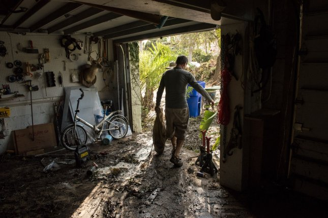 Paul Naron carries out damaged items from his flooded house September 11 after Hurricane Irma struck in Coconut Grove, Fla. The White House on Friday requested emergency disaster funding for the third time. File Photo by Ken Cedeno/UPI