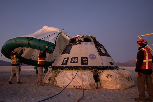 Boeing, NASA and U.S. Army personnel work around the Boeing CST-100 Starliner spacecraft shortly after it landed in White Sands, N.M., on Sunday. NASA Photo by Bill Ingalls/UPI