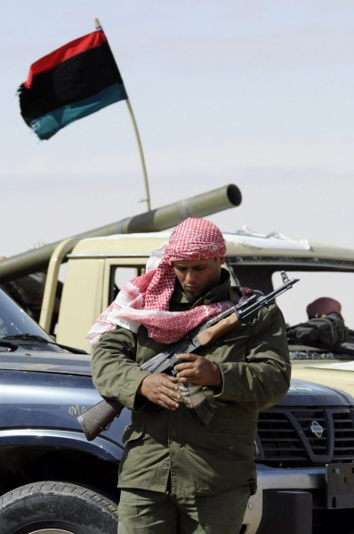 A Libyan rebel stand next to an armed vehicle at the western gate of the strategic restive town of Ajdabiya, on April 20, 2011. France and Italy joined Britain in sending military advisers to insurgent-held eastern Libya, as Tripoli warned that foreign boots on the ground would prolong the conflict. UPI\Tarek Alhuony.