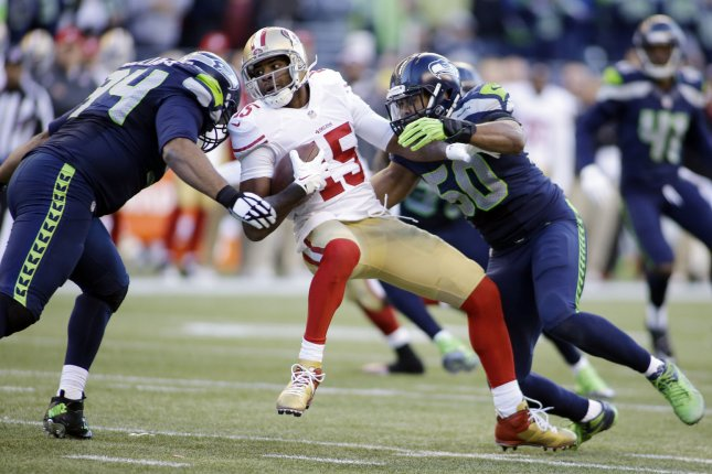 Seattle Seahawks defensive tackle Kevin Williams (94) and linebacker K.J. Wright team up to bring down San Francisco 49ers wide receiver Michael Crabtree (15) at CenturyLink Field in Seattle, Washington on December 14, 2014. UPI/Jim Bryant
