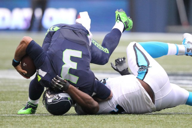 Seattle Seahawks quarterback Russell Wilson is turned on his head by Carolina Panthers defensive end Kony Ealy on October 18, 2015. The Seahawks have begun making moves on the o-line, resulting in new pieces at all five positions. Photo by Jim Bryant/UPI