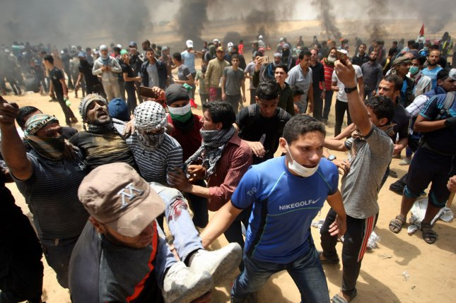 Palestinians carry an injured protester during a demonstration at the Gaza-Israel border on May 14, 2018. Israel's High Court of Justice ruled on Friday that use of live ammunition by Israeli troops during weekly protests at the border was justified. Photo by Ismael Mohamad/UPI