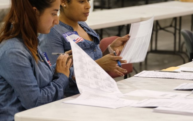 Palm Beach County election workers check ballots during a machine recount for both the governor and senate races in Florida on Monday. Photo by Gary I Rothstein/UPI