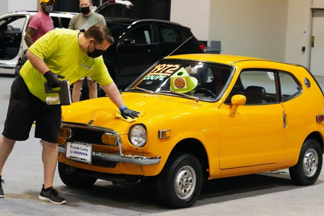 A worker cleans the fingerprints off of a 1972 Honda Coupe during the St. Louis Auto Show in St. Louis on April 9. A new report said Monday the age of U.S. vehicles on the road reached 12.1 years during the pandemic. Photo by Bill Greenblatt/UPI