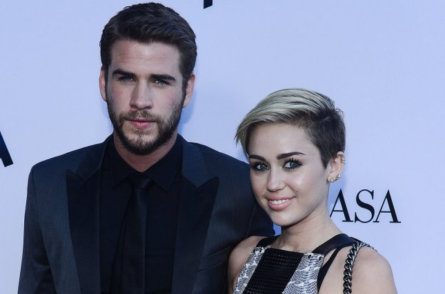 Miley Cyrus (R) and Liam Hemsworth at the Los Angeles premiere of Paranoia on August 8, 2013. The couple reportedly got engaged again in January. File Photo by Jim Ruymen/UPI