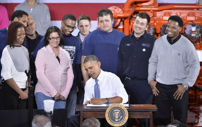 Surrounded by factory workers, U.S. President Barack Obama signs a Presidential Memorandum to initiate reform of federal job-training programs following a speech at General Electric's Waukesha Gas Engines plant in Waukesha, Wisconsin on January 30, 2014. In his speech, Obama emphasized the importance of training workers for the fastest growing occupations, as he built on the major themes of his State of the Union address in a two-day, four-state trip. UPI/Brian Kersey