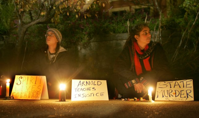 two women hold a vigil near the gates of San Quentin Prison where Stanley Tookie Williams is awaiting execution in San Quentin, CA on December 12, 2005. Williams is set for execution early December 13. (UPI Photo/Terry Schmitt)