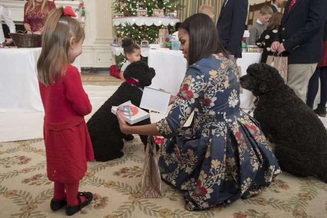 First lady Michelle Obama talks to a young girl as she welcomes military families and their children to the White House for a tour of the holiday decorations on Tuesday. Photo by Kevin Dietsch/UPI