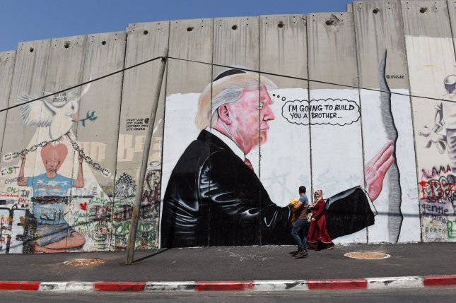 Palestinians walk past a mural of President Donald Trump on Israel's separation wall between Bethlehem and Jerusalem on Wednesday. Photo by Debbie Hill/UPI
