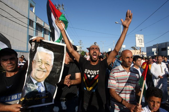 Protesters hold posters of Palestinian President Mahmoud Abbas during a July demonstration against Israel's West Bank annexation plans. File Photo by Ismael Mohamad/UPI