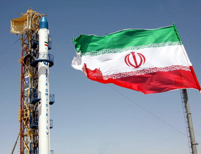 Iran's Safir-e-Omid (ambassador of hope) rocket, which is capable of carrying a satellite into orbit is seen next to Iran's flag before launch at Iran's space center in Tehran, Iran. (UPI Photo/Fars News Agency)