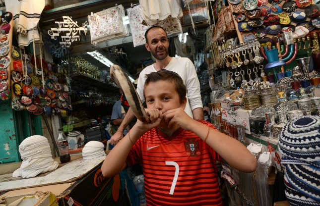 An Israeli boy blows a shofar, a ram's horn, in a shop in the Mahane Yehuda market in central Jerusalem, Israel, September 24, 2014. Jews will blow the shofar in synagogues during Rosh Hashanah, the Jewish New Year, services. UPI/Debbie Hill