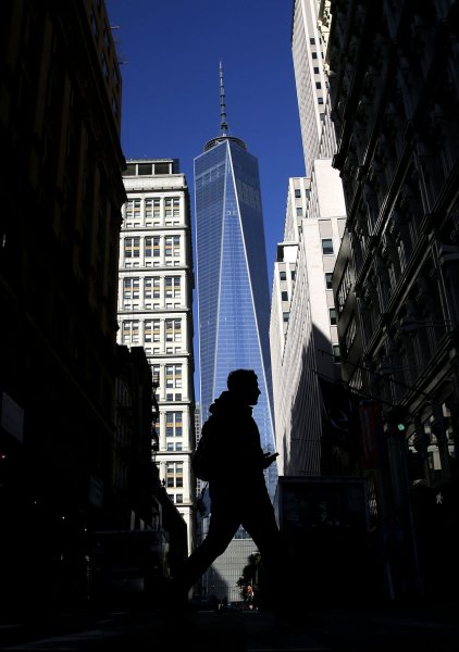A man crosses the street in the shadows of One World Trade Center in New York City on November 3, 2014, as the building officially opens. File Photo by John Angelillo/UPI