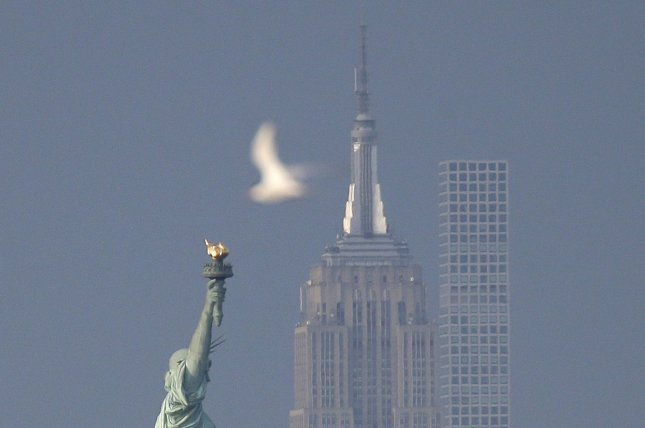 A bird moves past the Statue of Liberty, the Empire State Building and 432 Park Avenue in Bayonne, N.J., on Wednesday. Photo by John Angelillo/UPI