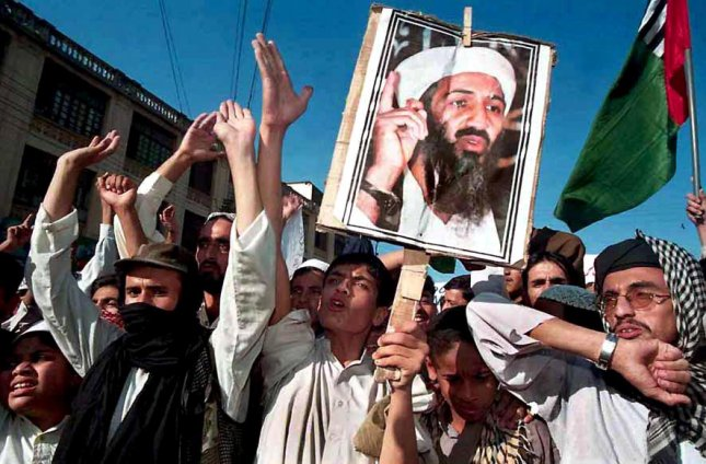 POY2001121936 - 19 DECEMBER 2001 - UPI PICTURES OF THE YEAR - FILE PHOTO - 24 NOVEMBER 2001 - KARACHI, PAKISTAN: Students of an Islamic school shout anti U.S. slogans as they hold a poster of terrorist suspect Osama bin Laden during a demonstration following Friday prayers in Karachi, Pakistan Nov. 23, 2001. mk/UPI