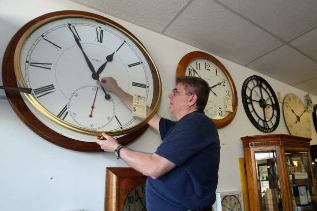 A Clock salesman sets the time on an oversized wall clock back one hour to Standard Time for the Winter. (UPI Photo/Bill Greenblatt)