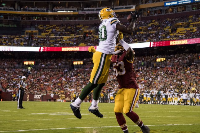 Green Bay Packers tight end Martellus Bennett brings in a touchdown pass against the Washington Redskins' Zach Brown in the first quarter of their preseason game on August 19 at FedEx Field in Landover, Md. Photo by Kevin Dietsch/UPI