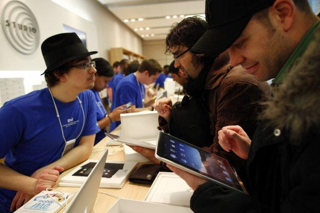 Apple employee Benjamin Salasek (L) talks with new iPad owner Miguel Bullon (C) as Pedro Cordero checks out his new iPad at Apple Computer's North Michgan Avenue store in Chicago on April 3, 2010. File Photo by Brian Kersey/UPI
