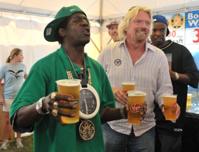Flava Flav (R) and Richard Branson serve beer at a vendor tent at the Virgin Mobil Freefest at the Merriweather Post Pavilion in Columbia, Maryland on August 30, 2009. UPI/Kevin Dietsch
