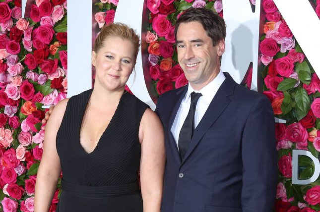 Amy Schumer (L), pictured with Chris Fischer, showed off her growing belly during an outing with friends. File Photo by Serena Xu-Ning/UPI
