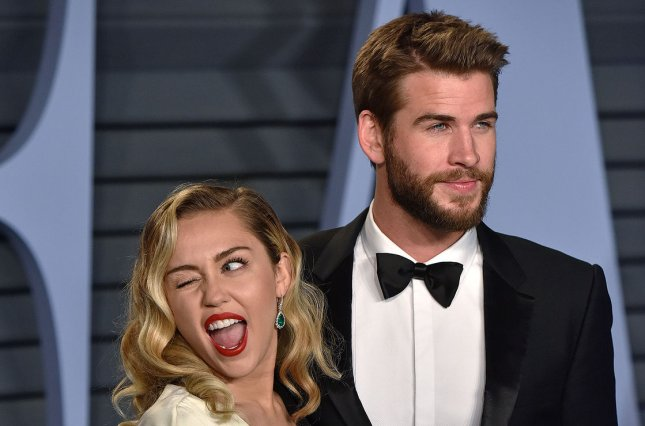 Liam Hemsworth (R), pictured with Miley Cyrus, failed to join the singer at the Grammy Awards on Sunday. File Photo by Christine Chew/UPI