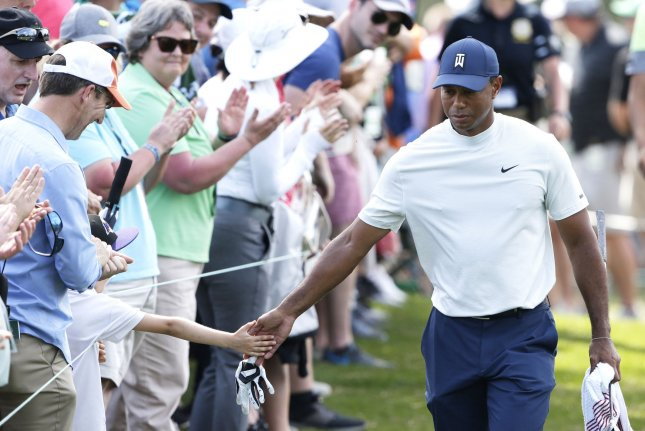 Tiger Woods touches the hand of a patron as he walks to the 8th tee box in the second round at the 2019 Masters Tournament on Friday at Augusta National Golf Club in Augusta, Georgia. Photo by John Angelillo/UPI