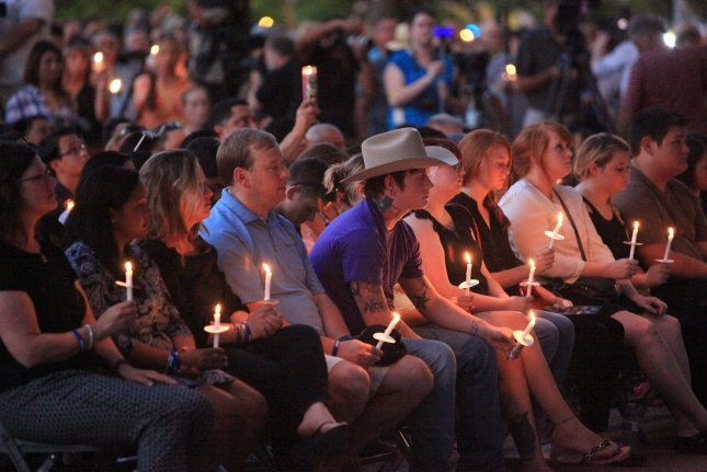Families of the five slain Dallas police officers hold candles during a candle light vigil outside City Hall in Dallas, Texas on Monday. A crowd of more than 1,000 people united in grief to honor the victims of last week's downtown ambush that killed five police officers during a demonstration. Photo by Chris McGathey/UPI
