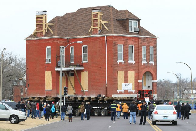 Sightseers watch as the 122 year-old home of Charlsetta Taylor makes a turn onto her new street while it is moved in St. Louis on February 26, 2017. The home is being relocated from the site where the new National Geospatial-Intelligence Agency (NGA) is to be built. The new 97-acre site will house 3,100 employees. Taylor's home built in 1895, is moving seven-tenths of a mile from its old location. Photo by Bill Greenblatt/UPI