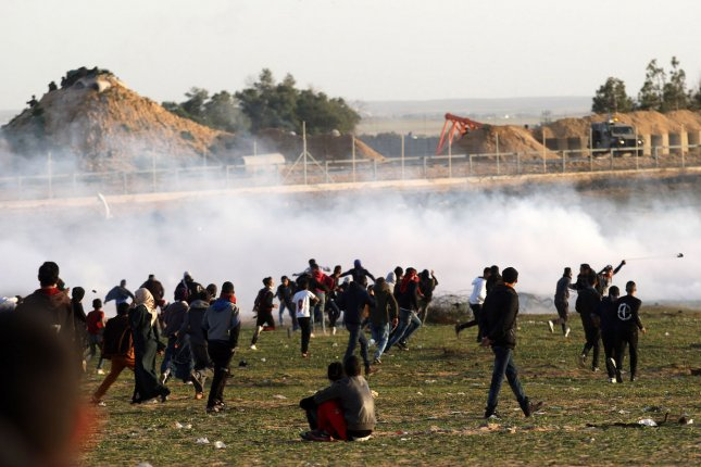 Palestinian demonstrators protest under tear gas canisters fired by Israeli forces during a demonstration near the fence along the border with Israel, east of Rafah, southern Gaza this month. Photo by Ismael Mohamad/UPI