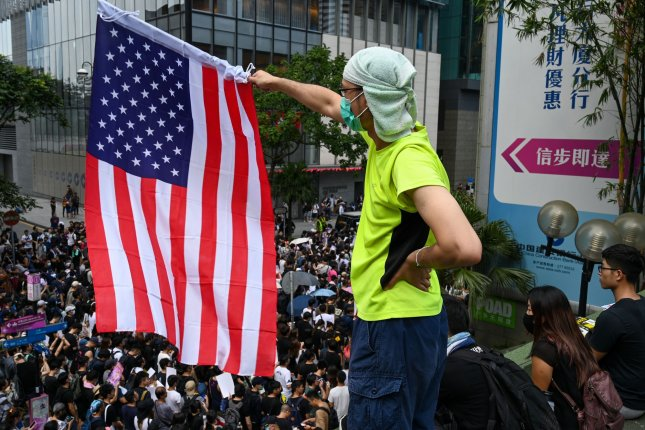 A demonstrator waves an American flag on Sunday in Hong Kong as a large rally around the U.S. Consulate called for support for their movement, which is seeking greater democracy and independence from Beijing. Photo by Thomas Maresca/UPI