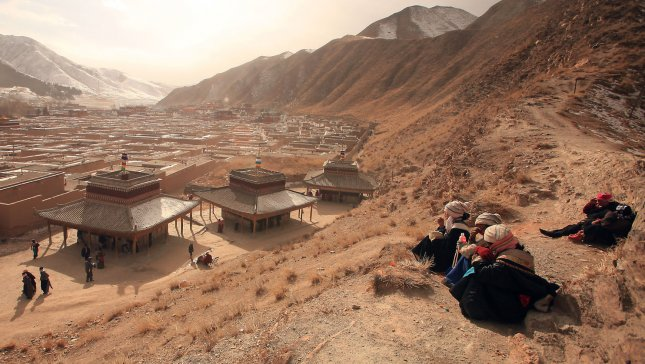 Tibetan women sit on a hill overlooking the Labrang Monastery on the Tibetan plateau, February 5, 2012. UPI/Stephen Shaver