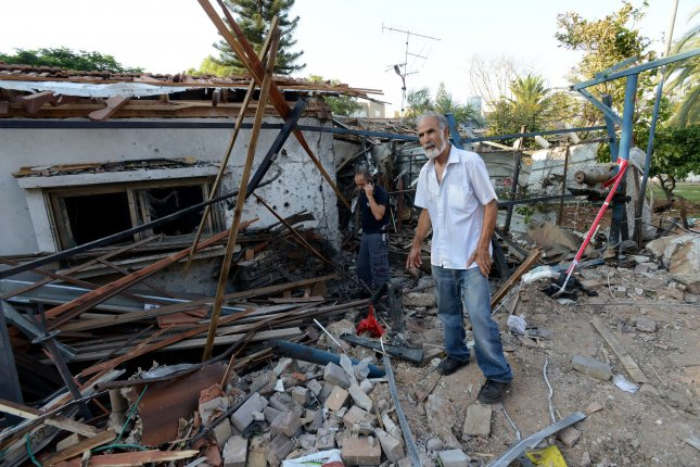 An Israeli stands in front of a house destroyed by a rocket fired by Palestinian militants in Gaza, in Yehud, near Ben Gurion Airport, Israel, July 22, 2014. The Federal Aviation Administration told U.S. airlines they are prohibited from flying to Tel Aviv's Ben Gurion Airport for 24 hours after the Hamas rocket hit the house in Yehud. Several European airlines have also suspended flights. UPI/Debbie Hill