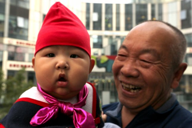 A proud grandfather holds his young grandson while shopping at an international mall in Beijing on October 29, 2015, after the announcement that the Chinese government would scrap its notorious one-child policy, which officially ended January 1, 2016. A year after the one-child policy was replaced with a two-child policy, China's birth rate increased 11.5 percent to its highest level since 2000. File Photo by Stephen Shaver/UPI