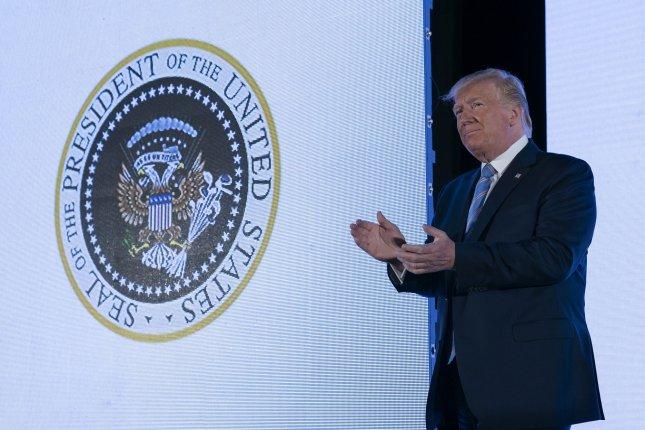President Donald Trump unknowingly stands in front of a presidential seal with Russian and golf imagery. Photo by Chris Kleponis/UPI