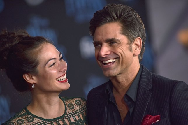 John Stamos, pictured with wife Caitlin McHugh, is slated to co-host the 40th anniversary installment of A Capitol Fourth, the annual Fourth of July concert broadcast on PBS. FilePhoto by Chris Chew/UPI