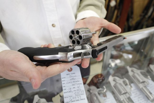 A gun shop owner holds a .357 magnum revolver at his store in Dundee, Ill. File Photo by Brian Kersey/UPI